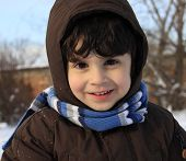 stock photo of auburn  - Preschool boy with auburn hair and brown eyes is playing with snow outside in a winter day - JPG