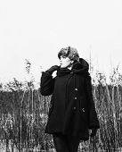 pic of cold-weather  - Fashion woman wearing a winter coat and fur cap and she posing front of the reeds cold rainy weather waist up black and white image - JPG