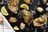 stock photo of clam  - Fresh oysters and clams on a black stone plate top view - JPG