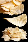 stock photo of crisps  - Collage of ridged fried potato crisps on black - JPG