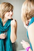 Постер, плакат: Pretty young woman applying mascara eyeshadows in front of a mirror