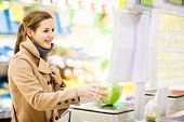 foto of grocery store  - Beautiful young woman shopping for fruits and vegetables in produce department of a grocery store - JPG