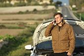 image of breakdown  - Guy calling roadside assistance for his breakdown car i a country road