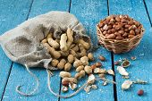 stock photo of groundnut  - Peanut pods in a linen bag groundnut seeds in a basket on blue wooden table - JPG