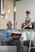 stock photo of grandpa  - Granddaughter helping disabled grandpa in domestic duties - JPG
