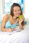 stock photo of nightgown  - young attractive and beautiful woman in nightgown lying on bed at bedroom holding apple writing diary with pen in relax looking tranquil and happy in American lifestyle concept - JPG