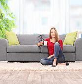 picture of early 20s  - Woman drinking coffee seated by a sofa at home shot with tilt and shift lens - JPG