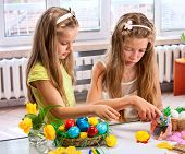 stock photo of sisters  - Children girl paint Easter eggs at home - JPG