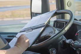 image of trucks  - Closeup view of the hands of truck driver who is is writing in the documentation driver - JPG