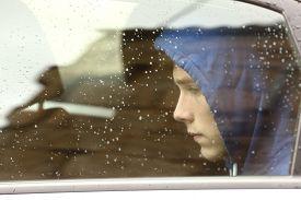 stock photo of sad  - Sad teenager boy worried inside a car looking through the window  - JPG