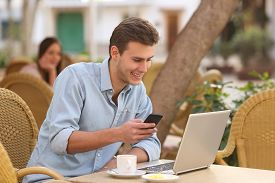 foto of self-employment  - Self employed happy man working with a laptop and a smart phone in a restaurant terrace  - JPG