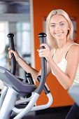 pic of elliptical  - Portrait of a beautiful young blond girl wearing a white top looking at the camera - JPG