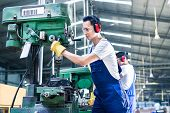image of production  - Asian worker in production plant drilling at machine on the factory floor - JPG
