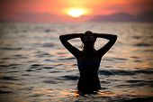 Beautiful woman in water embracing the golden sunshine glow of sunset, enjoying peace, serenity poster