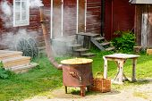 stock photo of boil  - Boiling water in large stove for outdoor laundry - JPG