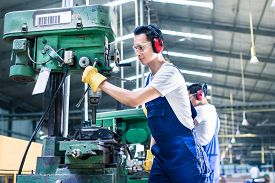 picture of production  - Asian worker in production plant drilling at machine on the factory floor - JPG