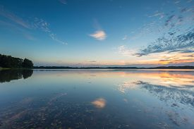 stock photo of cloudy  - Beautiful lake at sunset landscape with cloudy sky reflecting in water. Polish lake in Mazury lake district ** Note: Soft Focus at 100%, best at smaller sizes - JPG