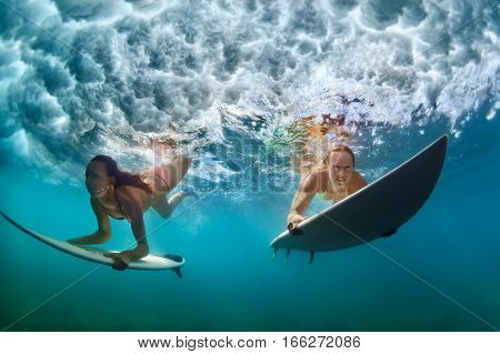 poster of Group of active girls in action. Surfer women with surf board dive underwater under breaking big wave. Healthy lifestyle. Water sport extreme surfing in adventure camp on family summer beach vacation