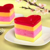 image of torta  - Colorful Peruvian heart-shaped jelly-pudding cakes called Torta Helada with a blooming peach branch in the back (Selective Focus Focus on the front of the first cake)
