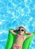 girl in the swimming pool in hat and sun glasses