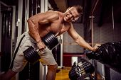 Strong Bodybuilder Doing Heavy Weight Exercise For Back With Dumbbell poster