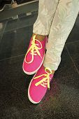 Legs Or Feet In Bright Pink Gumshoes Or Canvas Sneakers With Yellow Laces And Stylish Floral Jeans O poster