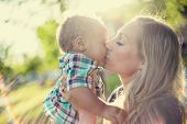 Beautiful Mother kissing her adorable baby boy in the sunset sunlight. Sun rays shining through as t poster