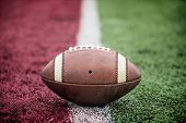 Closeup of an American Football resting on the goal line at a football stadium. Looks like its a tou poster