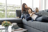 Asian Teenage Couple Make Eye Contact Relaxing On A Sofa  By The Window Relax In The Luxurious Room. poster