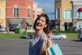 Happy Young Asian Woman Shopping An Outdoor Market With Background Of Pastel Buildings And Blue Sky. poster