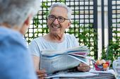 Senior couple reading newspaper during breakfast. Portrait of happy old man with grey hair reading t poster