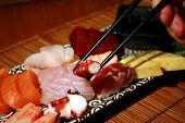image of yellowfin tuna  - A hand with chopsticks picks up a piece of raw octopus  - JPG