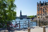 Bikes Near Bridge Railing And Stockholm City Hall (stadshuset) Tower Building Of Municipal Council A poster