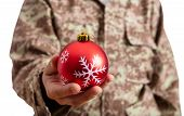 Young Soldier Holding A Red Christmas Ball Standing On White Background poster