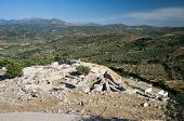 ruins of archaeological excavations of Mycenae on background view of cultivated land