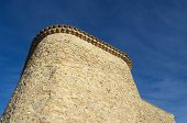 ancient stone wall of curve rear facade of church (apse) against blue sky