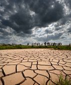 stock photo of loam  - stormy clouds dark are gathering on dry and cracked land - JPG