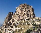 the Uchisar castle is a tall vulcanic rock outcrop riddled with tunnels and windows visible for mile