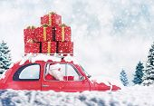 Santa Claus On A Red Car Full Of Christmas Present With Winter Background Drives To Deliver poster