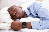 Close-up Of A Man Sleeping With Smart Watch In His Hand Showing Heartbeat Rate poster