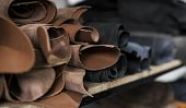 Different Pieces Of Leather In A Rolls. The Pieces Of The Colored Leathers. Rolls Of Natural Brown A poster