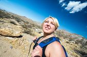 Female Blonde Hiker Spots To Squit To Look Off Into The Distance As She Hikes Through The California poster