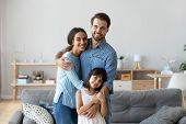 Whole Family Standing In Living Room Embracing Looking At Camera poster