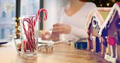 holidays and sweets concept - close up of candy canes and gingerbread houses at home over christmas  poster
