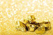 Golden Ingots Close Up On Golden Dust Glitter Background. Shiny Golden Nuggets On Golden Glitter Bac poster