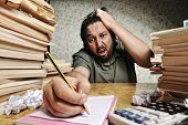 Businessman in problems. Alone working in office with a lot of books around on messy table. Yelling