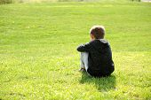 stock photo of autism  - Sad abandoned orphan sitting in nature and contemplating - JPG