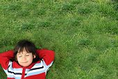 Little beautiful kid outdoor. Lay on green grass.