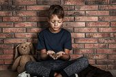 Poor Homeless Boy Holding Coins On Floor Near Brick Wall poster