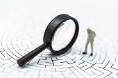 Miniature People: Businessman Use Magnifying Glass To Find The Route On The Maze. Concepts Of Findin poster